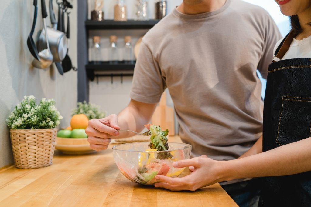 Pareja de hombre y mujer están de pie en la cocina preparando y comiendo una ensalada saludable.